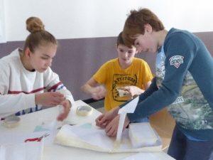 Kinder basteln ein Segelboot aus Papier - Teamwork