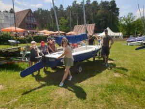 Segelboot wird mit Hilfe eines Slippwagens ins Wasser gelassen